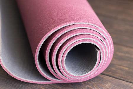 Rolled yoga mat on wooden floor, concept for start the doing Ashtanga yoga.