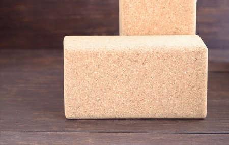 Two cork blocks for doing yoga on wooden floor. Yoga props background.