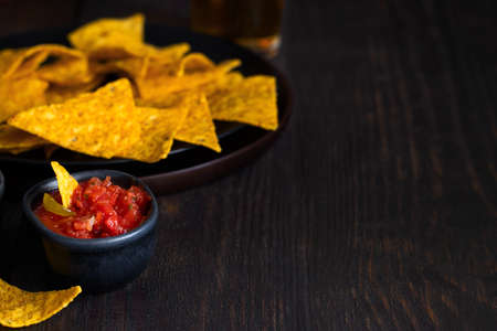 Red chilli sauces with nachos made with corn tortilla chips on the table. Totopos with avocado sauce Mexican dish background.Copy space