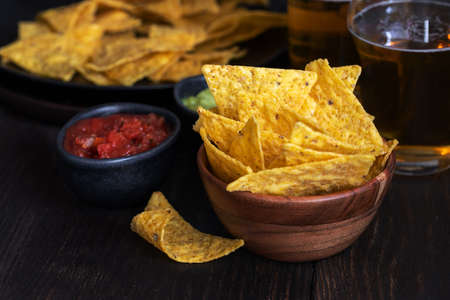 Nachos with guacamole, red chilli sauce and beer on wooden table The most famous Mexican snack background. Archivio Fotografico