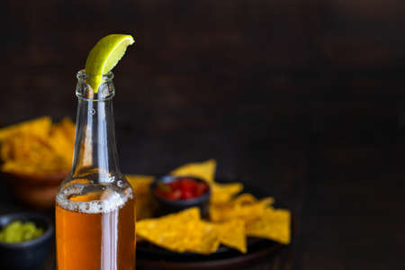 Mexican beer or bear with lime juice and Mexican snack nachos with guacamole. National food background.Copy space Archivio Fotografico