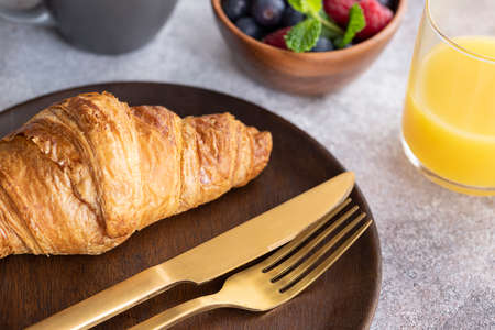 Close up of fresh baked croissant on wooden plate with gold cutlery. Typical ingredient for breakfast in cafe or restaurant. Archivio Fotografico