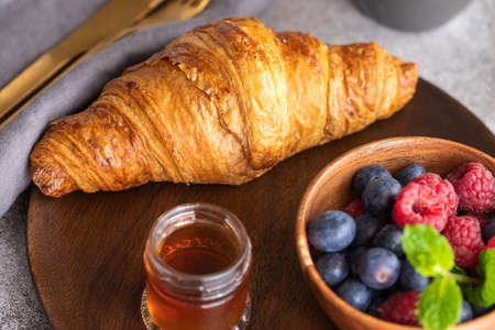 Fresh croissant, coffee with milk, berries, syrup and orange juice. Continental breakfast background.