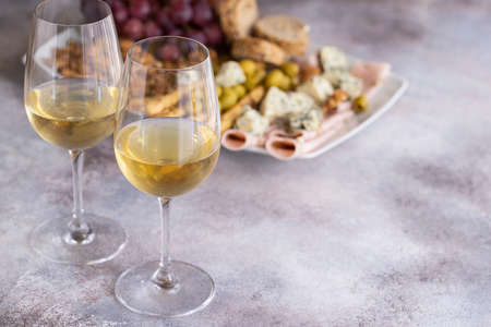 Two glasses of white wine and plate with different snacks. Blue cheese, olives, baguette slices, grissini, ham, grapes and nuts. Wine snacks set background.Copy space Archivio Fotografico