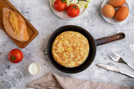Tortilla Spanish omelette made with eggs and potatoes on frying pan served with traditional salad, mayonnaise and bread. Spanish cuisine background. Archivio Fotografico