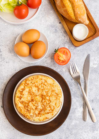 Tortilla, Spanish omelette made with eggs and potatoes on white table.