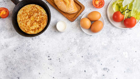 Tortilla Spanish omelette made with eggs and potatoes on frying pan served with traditional salad, mayonnaise and bread. Spanish cuisine background with copyspace. Archivio Fotografico