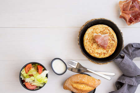 Frying pan with Tortilla, Spanish omelette made with eggs and potatoes and servedwith jamon, iberian ham. Top view.