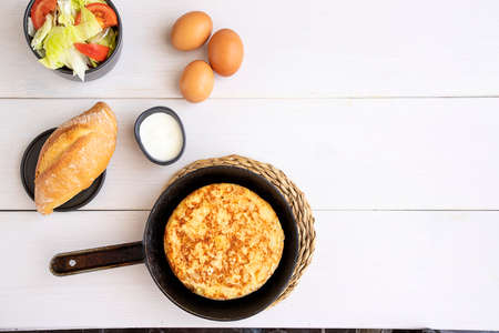 Top view of frying pan with Tortilla, Spanish omelette made with eggs and potatoes and served with salad and bread. Archivio Fotografico