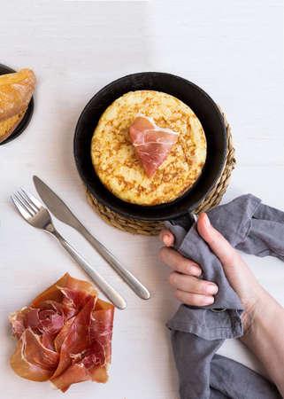 Women hand holding frying pan with Tortilla, Spanish omelette made with eggs and potatoes and servew with jamon, iberian ham. Top view.
