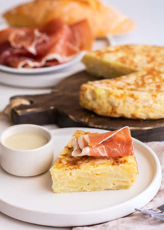 Tortilla, Spanish omelette made with eggs and potatoes. Traditional Spanish tapa served with mayonnaise and jamon, Iberian ham on white background.