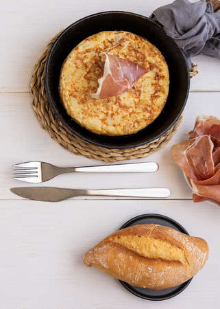 Frying pan with Tortilla, Spanish omelette made with eggs and potatoes and served with jamon, iberian ham. Top view.