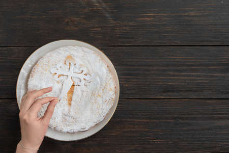 Woman hand put a silhouette cross for decorated Tarta de Santiago or St. James cake, famous spanish almond cake.