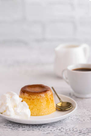 Creme caramel dessert or flan decorated with whipped cream and served with cup of coffee. Sweet moment vertical background.