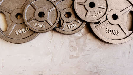 Weight plates for barbell or dumbbells in cement floor in gym. Equipment for weight training and building muscle. Concept for sport or workout with copy space.