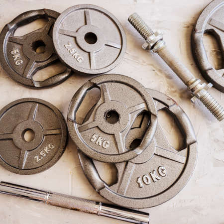Weight plates for barbell or dumbbells in cement floor in gym. Accessories for weight training and building muscle. Sport or workout concept background.