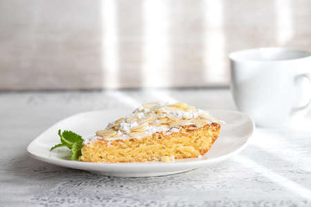 Homemade Almond cake slice on white plate and cup of coffee. Time for eat dessert background. Archivio Fotografico
