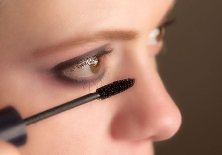 close-up of mascara brush about to be applied to eyelashes, selective focus on brush photo