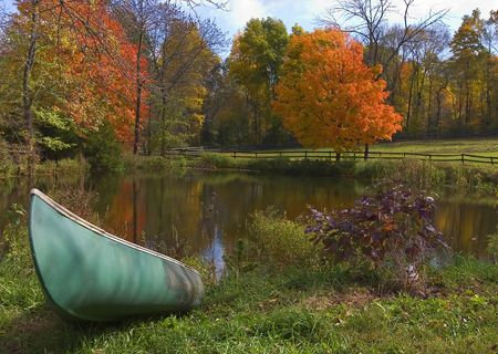 ashore: boat ashore a pond in upstate New York, with fall foliage