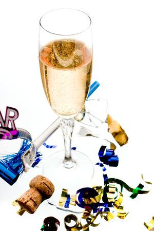 noisemaker: bubbly, golden champagne in one flute on white ground amongst confetti, cork and noisemaker. Stock Photo