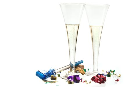 noisemaker: Ring in the New Year with a champagne toast! Two champagne flutes with confetti and a noisemaker on white ground with some reflection.