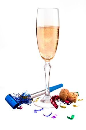 cheers! champagne in a flute on white ground with noisemaker, ribbon confetti and cork. Stockfoto