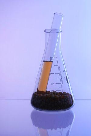 bio-fuel made from corn inside on test tube tha is inside of beaker full of corn kernels on cool ground