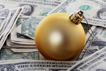 commercialism: Christmas Ball Ornament on Top of American Money, commercialism concept.