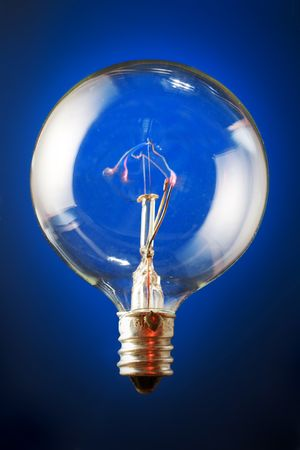 filament: Edisons filament bulb on blue gradient background. Stock Photo