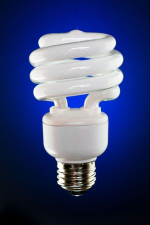 resourceful: Spiral compact fluorescent lamp on deep blue gradient background. Stock Photo