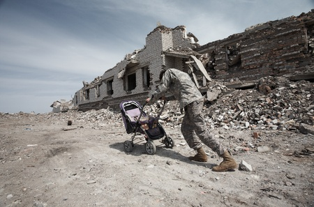 Man among the ruined buildings takes bricks