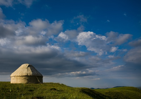 Kazakh yurt stands on the background of a beautiful blue sky with clouds