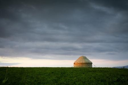Kazakh yurt stands on a green meadow under cloudy sky