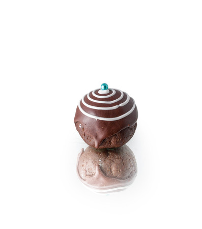 Dessert rum ball coated with dark chocolate, isolated on white background Stock Photo
