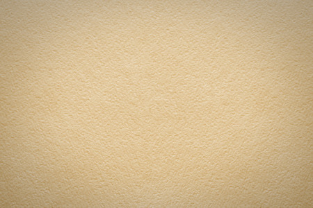 Background of watercolor paper  light beige color with a characteristic grain texture and small dark areas at the corners photo