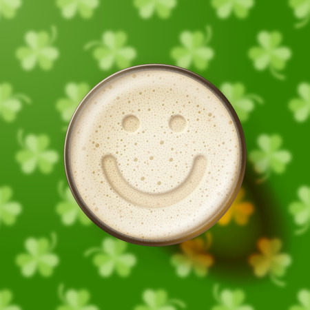 intoxicating: Glass of beer with smiling face on frothy top, on green background with clover leaves. St. Patricks Day and good mood concept