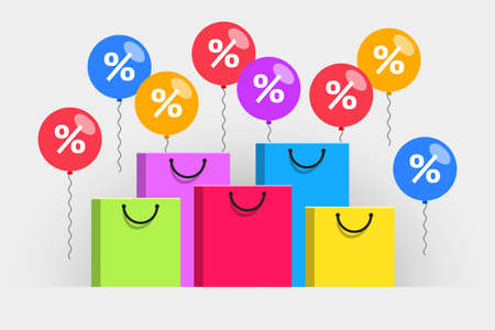 Colored paper shopping bags and balloons with white percent signs over gray background. Concept of seasonal discounts, promotions and sales, holiday shopping