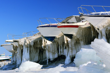 global cooling: boats on the shore in the winter ice-covered parking lot