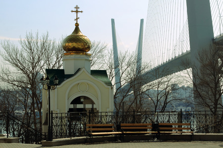 belfry: belfry of the Assumption of Our Lady on the background of the bridge supports in Vladivostok Stock Photo