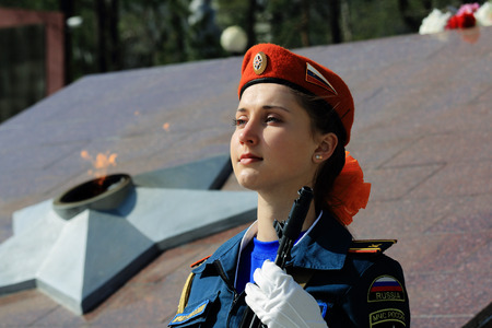 beautiful girl cadet the Russian Emergencies Ministry with arms in the honor guard at the Eternal Flame at the memorial in Vladivostok victory 07.05.2015 years