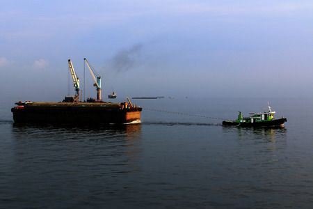 barge: a small tugboat pulling a barge loaded