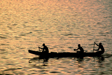 Drie Afrikanen roeien roeispanen in een lange boot in de avond bij zonsondergang