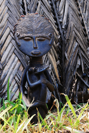 ebony: The African statuette of the Madonna nursing the infant chest carved from ebony amid mats made of palm branches