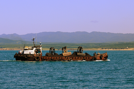 crane bucket: A barge loaded with coal at the roadstead of the island of Sakhalin Stock Photo