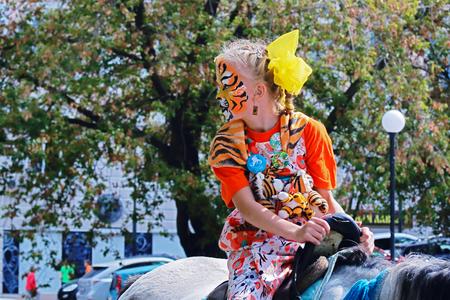 Mädchen auf einem Pferd mit gemaltem Gesicht unter einem Tiger in einem Tiger Tag in Wladiwostok am 27. September 2015 Tion in den Schutz des sibirischen Tigers ist seit 1999 in Russland stattgefunden.