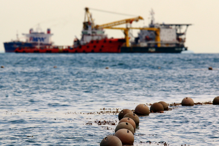 floats: the fence of floats on the beach of the sea with anchored ships