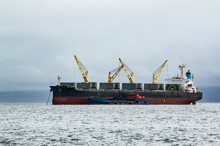 crane bucket: transshipment of coal from barges to large bulk carrier on the roads of Sakhalin island Stock Photo