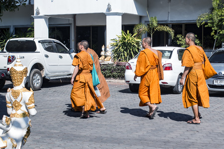 vows: four young monks walking on the street in Thailand Editorial