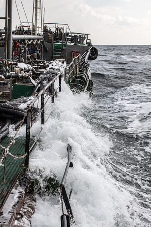 sea wave flooded the side of the tanker Stock Photo