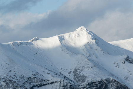 vertex: the top of the volcano is covered with snow and sunlit